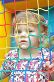 Young girl in bounce house. Young girl with face pressed upto the side of a bounce house Stock Photo