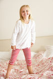 Young Girl Bouncing On Bed. Smiling To Camera Stock Images