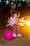 Young Girl Bouncing on a Big Pink Ball with the Sun Setting Behind Her. A young girl bounces on a large, pink ball with the sun setting behind her. It is golder stock photography