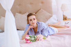 Young girl with bouquet of flowers on the bed. Beautiful young girl with bouquet of pink and white tulips lying on the bed royalty free stock photo