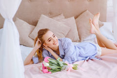 Young girl with bouquet of flowers on the bed. Beautiful young girl with bouquet of pink and white tulips lying on the bed royalty free stock photography