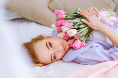 Young girl with bouquet of flowers on the bed. Beautiful young girl with bouquet of pink and white tulips lying on the bed stock photos