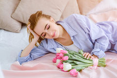 Young girl with bouquet of flowers on the bed. Beautiful young girl with bouquet of pink and white tulips lying on the bed royalty free stock image