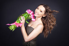 Young girl with a bouquet of flowers on black background Stock Photos