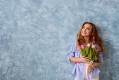 Young girl with bouquet of flowers on the blue wall background. Beautiful young girl with bouquet of tulips on the blue wall background. Wide shot with copy stock photo