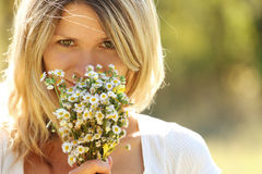 Young girl with a bouquet of flowers in nature Stock Photo