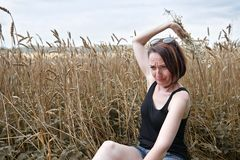 A young girl with a bouquet of flowers sitting near a wheat field. She picks off flower petals and wondering love or not love usin. G old folk legends and royalty free stock photos