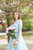 Young girl with a bouquet of peonies in the park, garden. Summer, spring Royalty Free Stock Photos