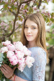 Young girl with a bouquet of peonies in the park, garden. Summer, spring Stock Image