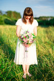 Young girl with bouquet in white dress stands in the middle of the field with his head down. Sadness, loneliness Royalty Free Stock Photography
