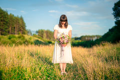 Young girl with bouquet in white dress stands in the middle of the field with his head down. Sadness, loneliness Royalty Free Stock Photos