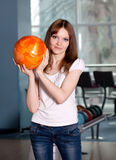 Young girl with bowling ball. Young preaty girl with bowling ball, standing on the playing line Stock Images
