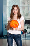 Young girl with bowling ball in hands. Young preaty girl with bowling ball in hands, standing on the playing line Stock Images