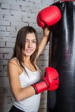 Young girl with boxing gloves. Girl posing with a punching bag Stock Photo