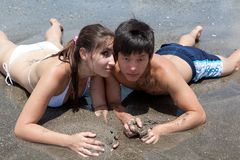 Young girl and boy on the beach Stock Photos
