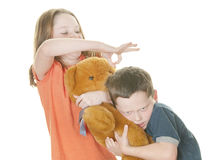 Young girl and boy fighting over bear Stock Images