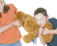 Young girl and boy fighting over bear Royalty Free Stock Image