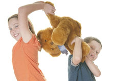 Young girl and boy fighting over bear Stock Photos
