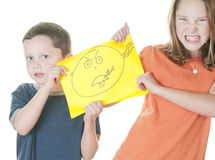 Young girl and boy fighting over drawing. Young girl and boy figting over drawing Royalty Free Stock Photos