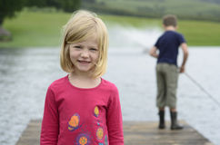 Young girl and boy fishing on wooden pier Stock Photos
