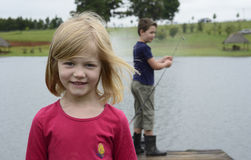 Young girl and boy fishing on wooden pier Stock Photography