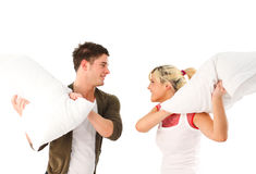 Young girl and boy having a pillow fight. In bed stock images