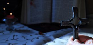 A young girl or a boy holds a cross in hands and prays at night. The background is an open old Bible book and nearby is candle wit. H flame. Close up religious Stock Image
