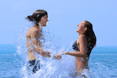 Young girl and boy jump out from water. Stock Photo