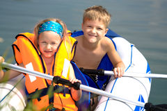 Young girl and boy at a lake. Young girl lifejacket and boy boating on the kayak on the lake Stock Photos