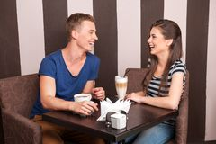 Young girl and boy laughing in cafe. stock photos