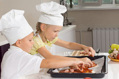Young girl and boy loading ingredients onto pizza Stock Photography