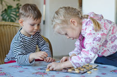 Young girl and boy playing checkers together Stock Image