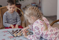 Young girl and boy playing checkers together Stock Images