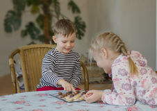 Young girl and boy playing checkers together Stock Photo
