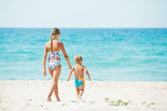 Young girl and boy playing happily at pretty beach Stock Images