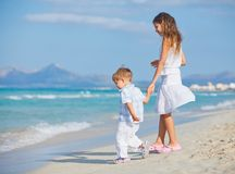 Young girl and boy playing happily at pretty beach Stock Photo