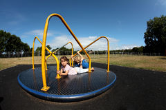 Young girl and boy playing on roundabout. Two children playing on roundabout in sunny family park or playground Stock Photography