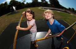 Young girl and boy playing on roundabout. Two children playing on roundabout in sunny family park or playground Royalty Free Stock Images