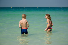 A young girl and boy plays in the sea together Royalty Free Stock Photos