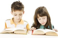 Young girl and boy reading the books on the desk Royalty Free Stock Photography