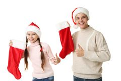Young girl and boy in santa hats. Holding christmas socks on white background Royalty Free Stock Photo