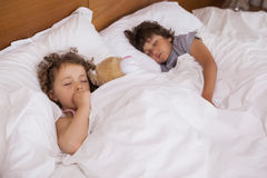 Young girl and boy sleeping in bed Royalty Free Stock Photos