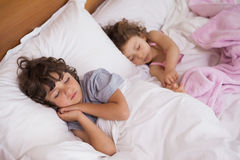 Young girl and boy sleeping in bed Royalty Free Stock Images