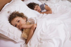 Young girl and boy sleeping in bed. Portrait of a young girl and boy sleeping in bed at home Stock Image
