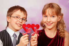 Young girl and boy with two heart shape lollipops. Funny portrait of young girl and boy with two red heart shape lollipops Royalty Free Stock Images