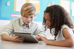 Young girl and boy using tablet in elementary school class stock images