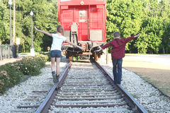 Young Girl and Boy Walking on RailRoad Tracks Royalty Free Stock Photos