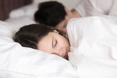Young girl with boyfriend sleeping peacefully in cozy white bed Royalty Free Stock Photos
