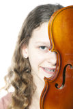 Young girl with braces behind violin. Young girl with braces looks from behind violin in studio Stock Images