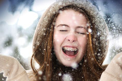 A young girl with braces throwing up snow in the air with a fur hood. Royalty Free Stock Photography